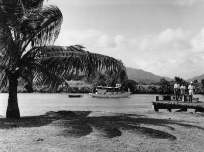 Photograph of  a small boat, people on a jetty and a palm treeReeves having leis pplaced around their necks by TEAL stewardesses