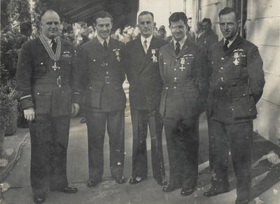 Photograph of Geoff Roberts and four other men after being awarded medals
