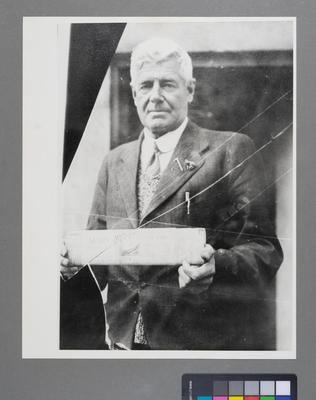 [Rodolph Wigley holding a newspaper headlining the first flight of an aero service to Mt. Cook/Aoraki]