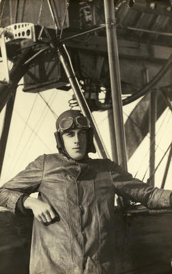 """Black and white photograph of L. C. C. Field, graduate of the Walsh Brothers Flying School, wearing pilot's clothing standing by a Walsh Flying boat """"D'"""