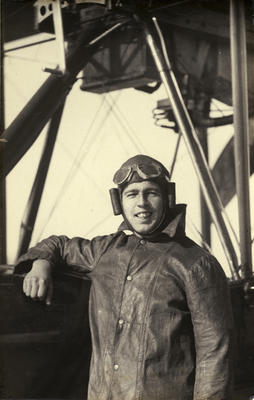 """Black and white photograph of Eric Strain, graduate of the Walsh Brothers Flying School, wearing pilot's clothing standing by a """" Roberts """" flying boat"""