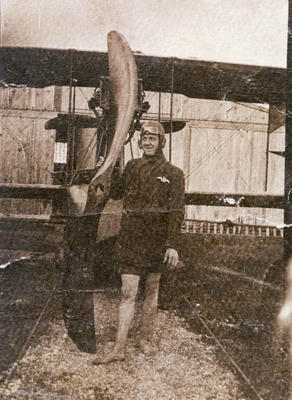Colour photograph taken of a photograph in an album, showing a man (Jack Russell?) standing next to a propeller