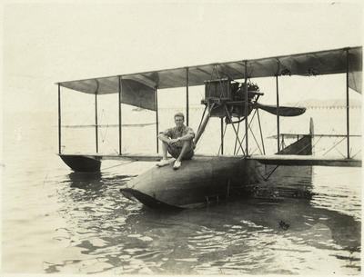 Black and white photograph of a man sitting cross-legged on the nose of a Curtiss flying boat