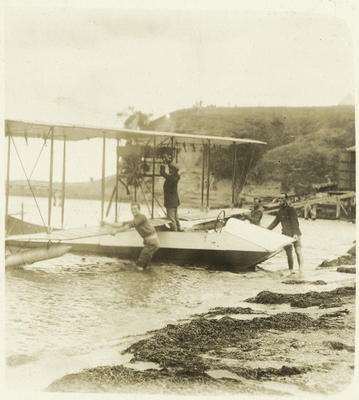 Black and white postcard showing four men alongside a Walsh Brothers Flying School seaplane on the beach