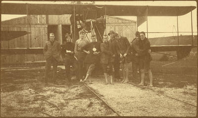 [New Zealand Flying School pilots in front of a seaplane on the rails leading to the sea]