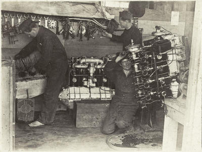 Black and white photograph of three men working on engines at  the Walsh Brothers Flying School workshop