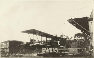 """Black and white photograph of a """"Boeing 1 F """"  flying boat outside the buildings of the Walsh Brothers Flying School"""