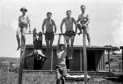 [Black and white negative of students of the New Zealand Flying School exercising on a bar]
