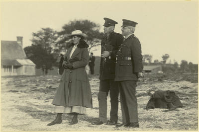 Black and white photograph of two men in uniform and a woman standing