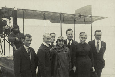 Black and white photograph of Vivian Walsh, left and Leo Walsh, right with five unidentified people in between, one in flying clothing, who could be sister Doreen Monica Walsh. Plane and pilot in background