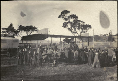 """Black and white photograph of a large group of people standing  flying boat """"B""""  at the Walsh Brothers Flying School"""