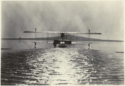 Black and white photograph of a Walsh Brothers Flying School Curtiss flying boat  taking off, with Rangitoto Island in the background
