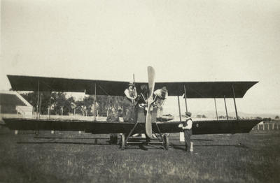 Black and white photograph of an aeroplane (DH 6?) that has landed on a racetrack, with men on it and around it including George Bolt (?)