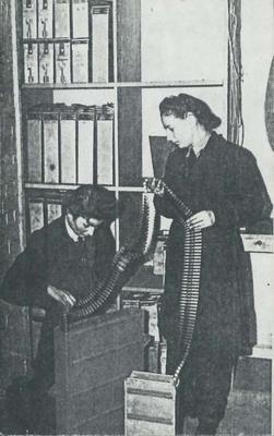 Two women WAAFs packing belts of bullets