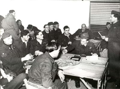Squadron crews being briefed around a table