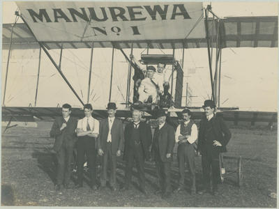 Photograph of Vivian Walsh at the controls of Manurewa No. 1. with Leo behind him and seven supports standing in front