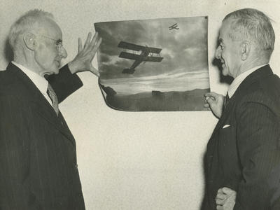 Photograph of Leo and Vivian Walsh looking at a picture of bi-planes