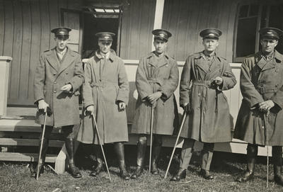 Photograph of a group of five men in Air Force uniforms with walking sticks outside a building with a verandah