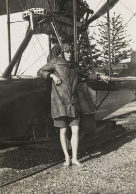 Photograph of a man leaning on a Curtiss flying boat bi-plane