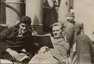 Photograph of two men reclining on the deck of a boat with another man partly obscured in background
