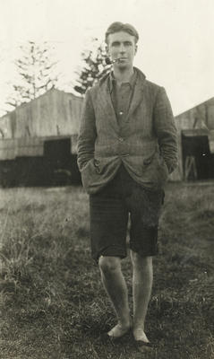 Photograph of man with pipe in his mouth standing in front of New Zealand Flying School hangars