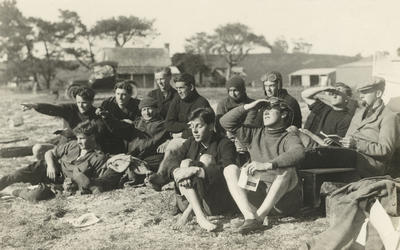 Photograph of a group of twelve men sitting and reclining on grass