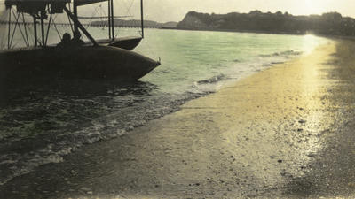 Photograph of a Curtiss flying boat bi-plane close to the beach