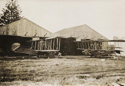 Photograph of two Curtiss flying boat bi-planes facing each other outside hangars