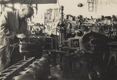 [Leo Walsh working on an engine in a workshop]