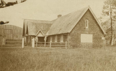 Photograph of Mission house with New Zealand Flying School hangar in background