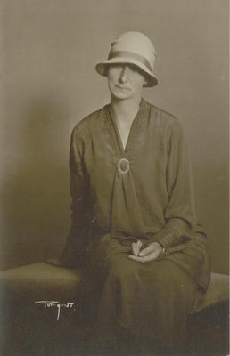Studio portrait of a seated woman wearing a cloche style hat
