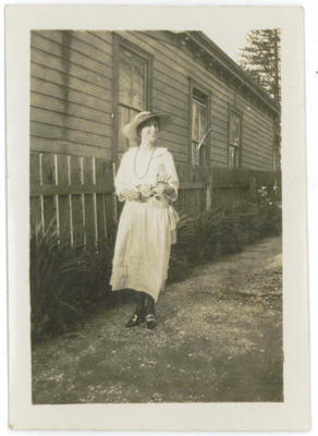 Woman dressed in white on path outside a house