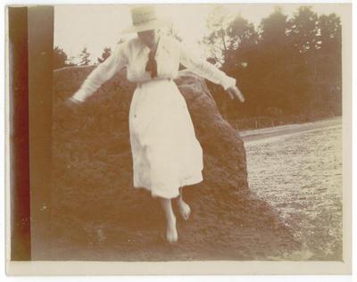 Woman walking on rocks beside water