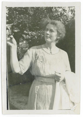 Woman with jacket over arm looking at shrubbery in garden
