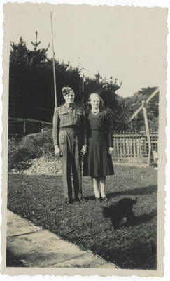 Photograph of a man in army uniform next to a woman in a garden with black cat walking in front