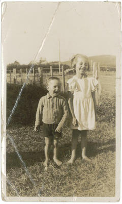 Two children, one older girl and a younger boy, barefoot and laughing in a paddock