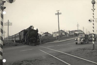 Steam locomotive WAB 769 and passenger train at level crossing, 1954