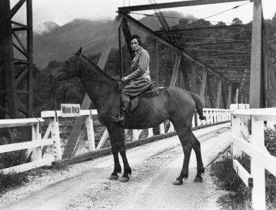[Jean Batten riding a horse over a bridge crossing Waiho River, Franz Josef / Waiau]