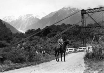 [Jean Batten riding a horse approaching a bridge crossing Waiho River, Franz Josef / Waiau]