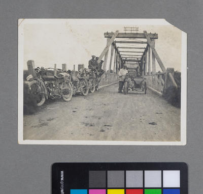 [Group of unidentified males and motorcycles by bridge]