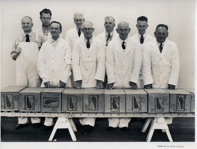 [Eight men in white coats, and one in white overalls, standing behind nine cartons of butter]