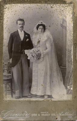 Portrait photograph of man and woman. Woman wearing wedding dress
