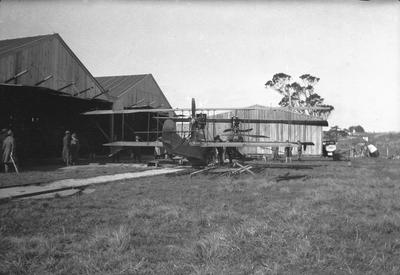 [Negative of seaplane outside hangars at the Walsh Brothers Flying School]