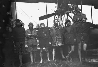 [Negative of Walsh Brothers Flying School trainees beside a plane]