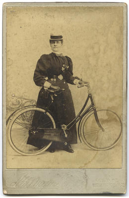 [Studio portrait of an unidentified woman with a bicycle]