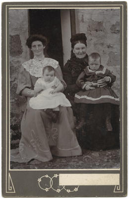Photograph of two woman with baby and young child