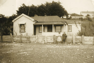 Photograph of a house with two woman