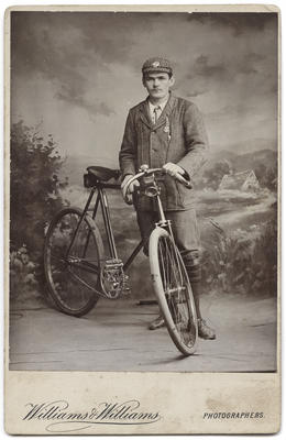 [Studio portrait of an unidentified male with a bicycle]