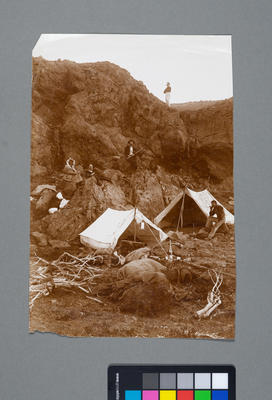 [Black and white photograph of camp in mountainous terrain]