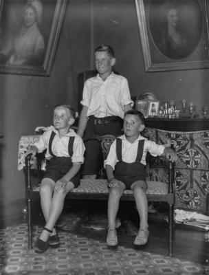 Portrait of two boys and an adolescent in a living room
